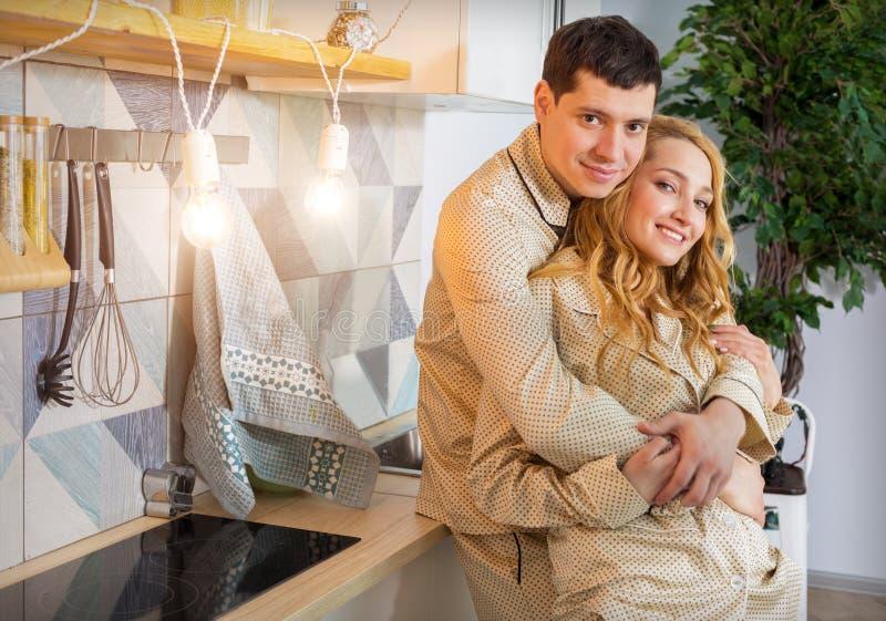 Pares en amor en los mismos pijamas en cocina fotos de archivo