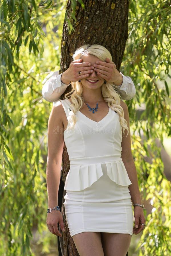 Pares en amor Ojos cubiertos hombre de la mujer rubia sonriente por sus manos en parque foto de archivo