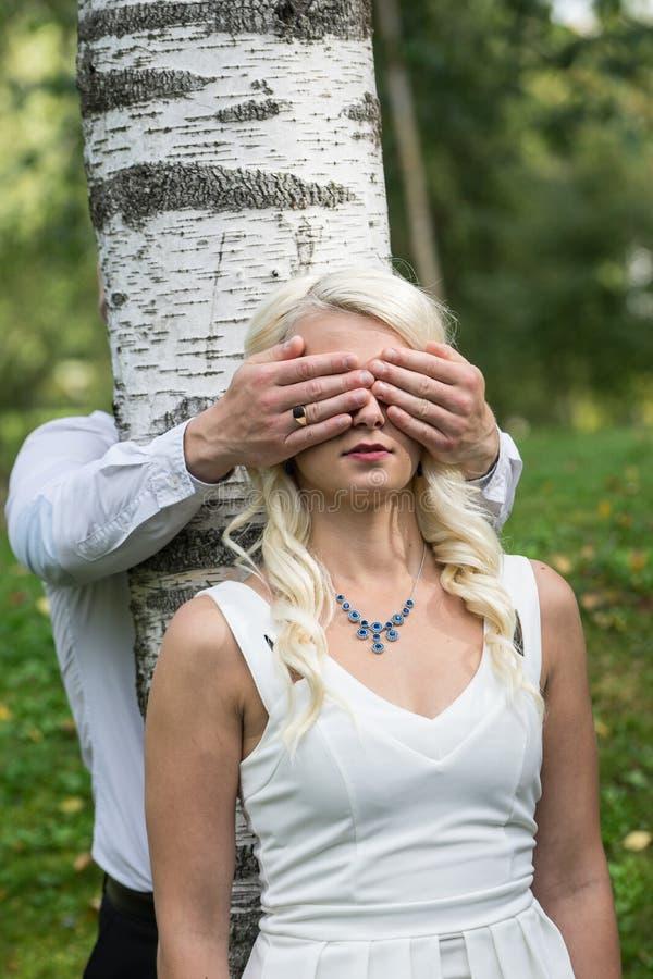 Pares en amor Ojos cubiertos hombre de la mujer rubia sonriente por sus manos en parque fotos de archivo