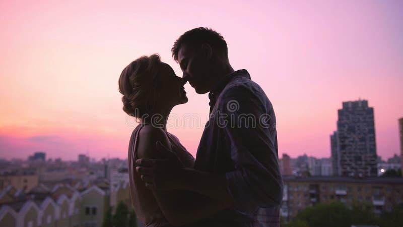 Pares en besarse del amor suavemente, colocándose en el tejado de la casa, puesta del sol hermosa foto de archivo