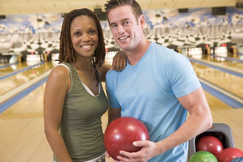 Pares en bola y la sonrisa de la explotación agrícola del callejón de bowling foto de archivo