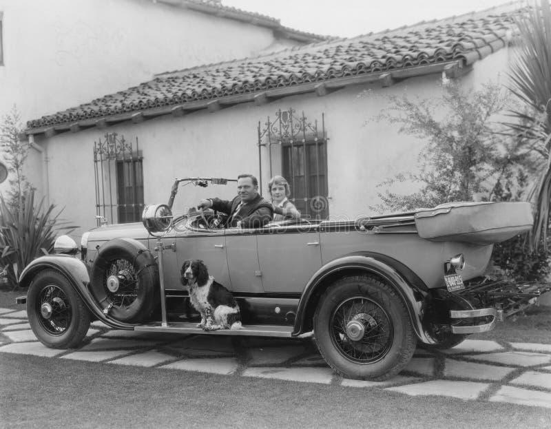 Pares en coche con el perro imagenes de archivo