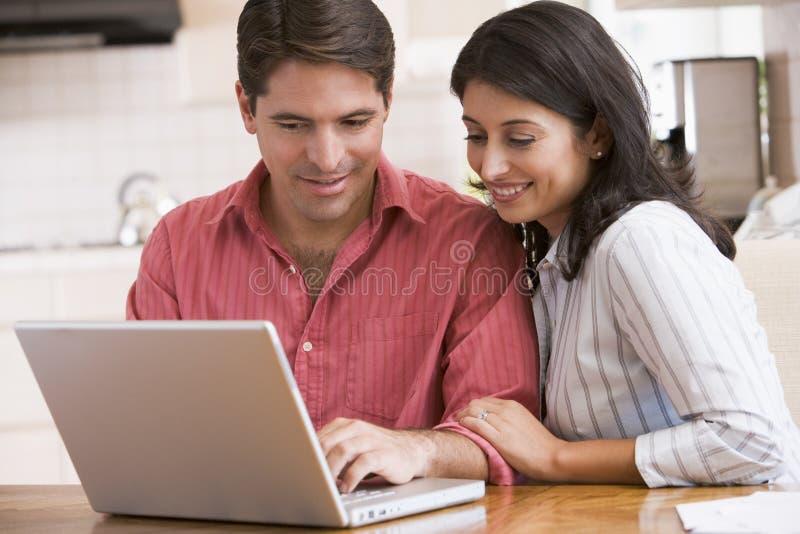 Pares en cocina con la sonrisa de la computadora portátil imagen de archivo libre de regalías