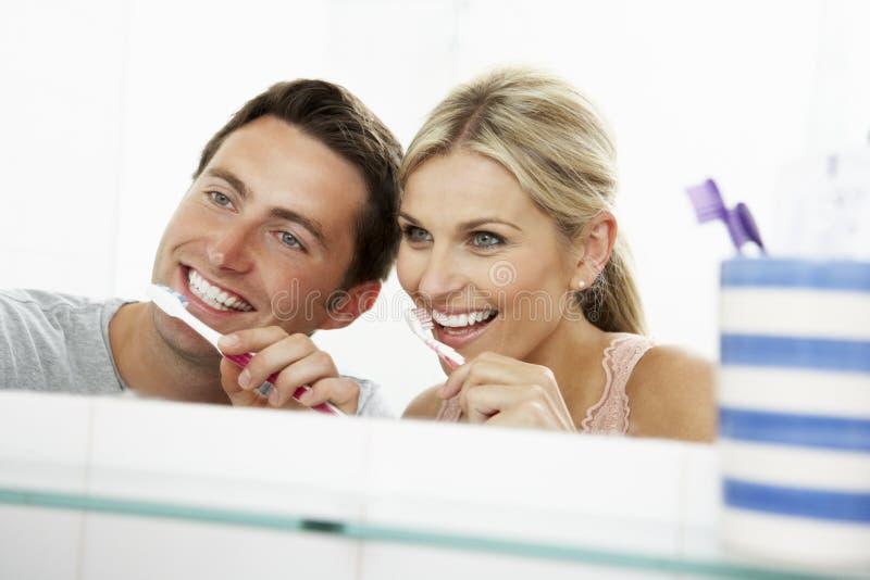 Pares en dientes que aplican con brocha del cuarto de baño imágenes de archivo libres de regalías