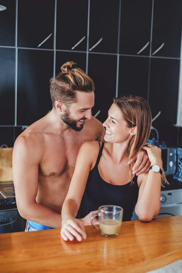 Pares en el amor que abraza en la cocina imagen de archivo libre de regalías