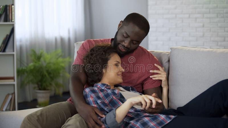 Pares en el amor que abraza en el sofá, disfrutando de dulzura y del amor junto, matrimonio fotos de archivo libres de regalías