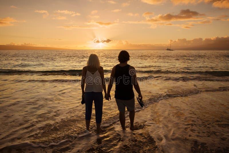 Pares en el amor que camina a lo largo de la playa junto en la puesta del sol imagenes de archivo