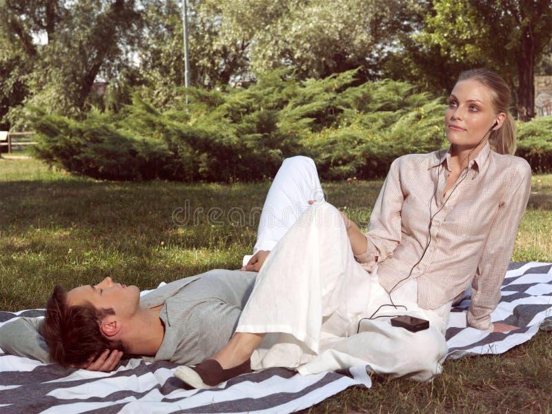 Pares en el amor que descansa en el parque imagen de archivo libre de regalías