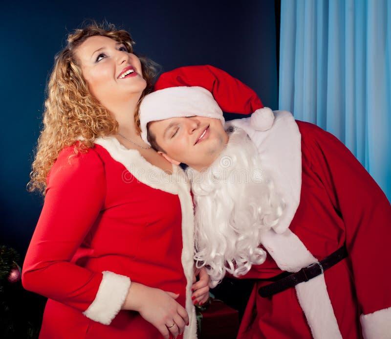Pares en el amor que desgasta los sombreros de Santa fotos de archivo libres de regalías