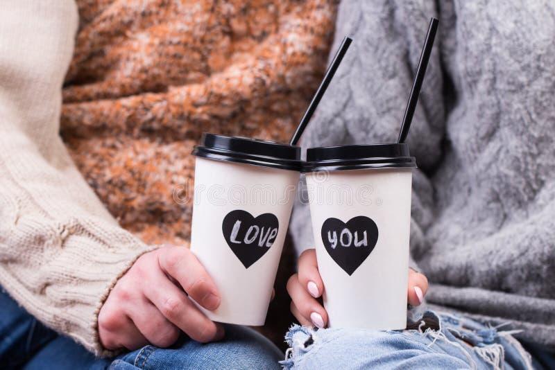 Pares en el amor que lleva a cabo las manos con café imagenes de archivo