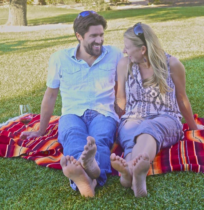 Pares en el amor que merienda en el campo en el parque imagen de archivo libre de regalías