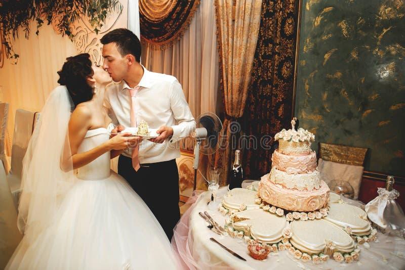 Pares en el amor que se besa cerca del pastel de bodas imágenes de archivo libres de regalías