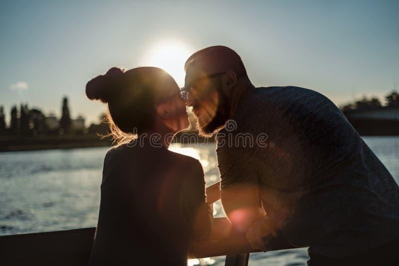 Pares en el amor que se besa por el río en la puesta del sol fotografía de archivo