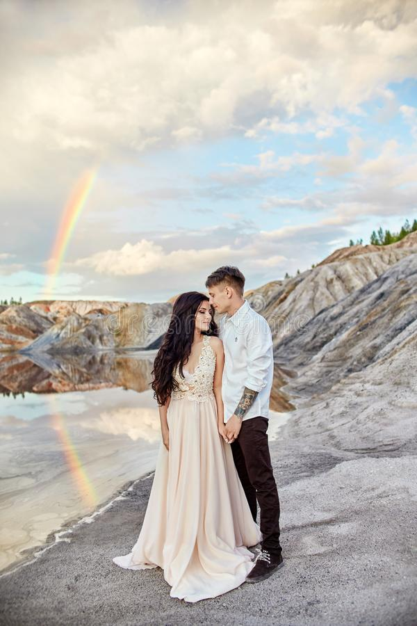 Pares en el amor que se besa y que abraza en el fondo del arco iris y de las montañas Un hombre y un amor de la mujer fabuloso imágenes de archivo libres de regalías