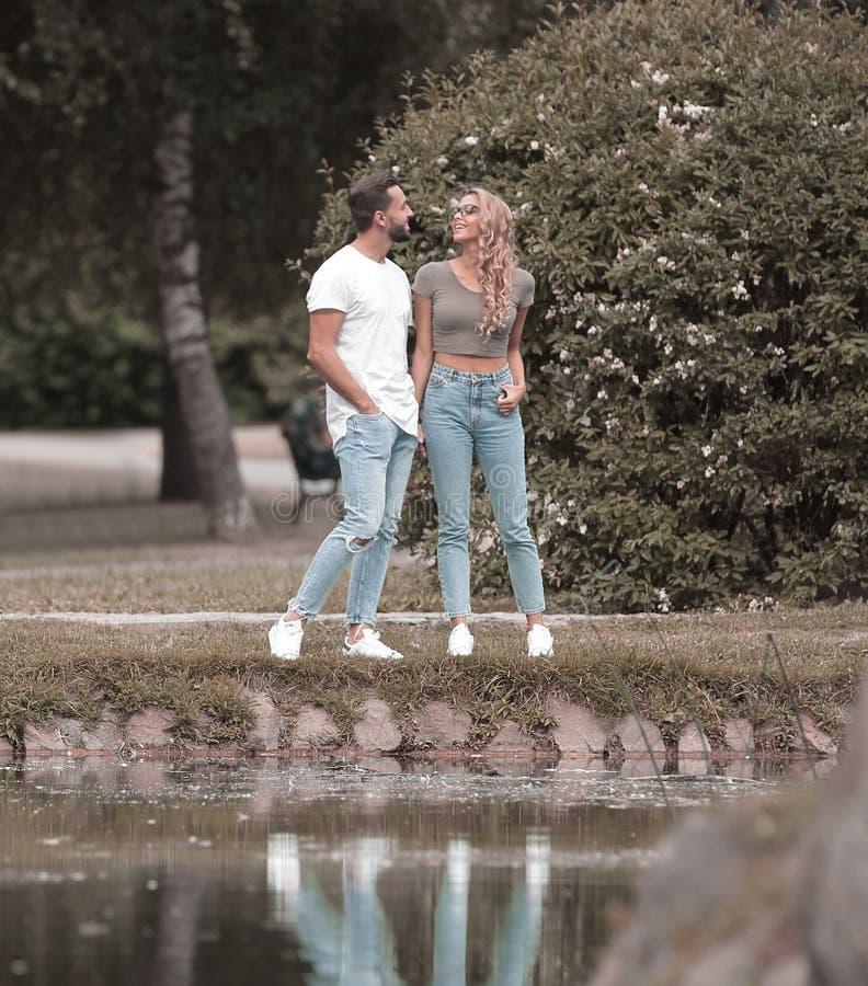 Pares en el amor que se coloca en la hierba cerca del lago foto de archivo libre de regalías