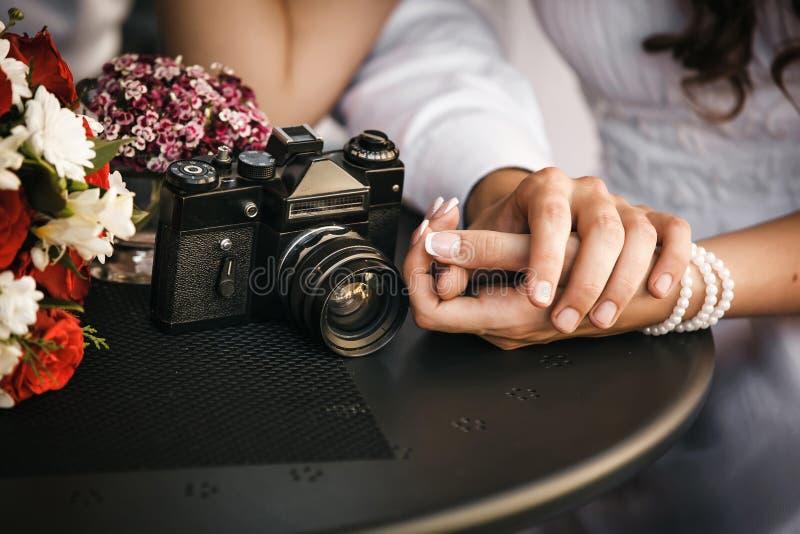 Pares en el amor que se sienta en el café, llevando a cabo la mano de cada uno Conce fotos de archivo libres de regalías