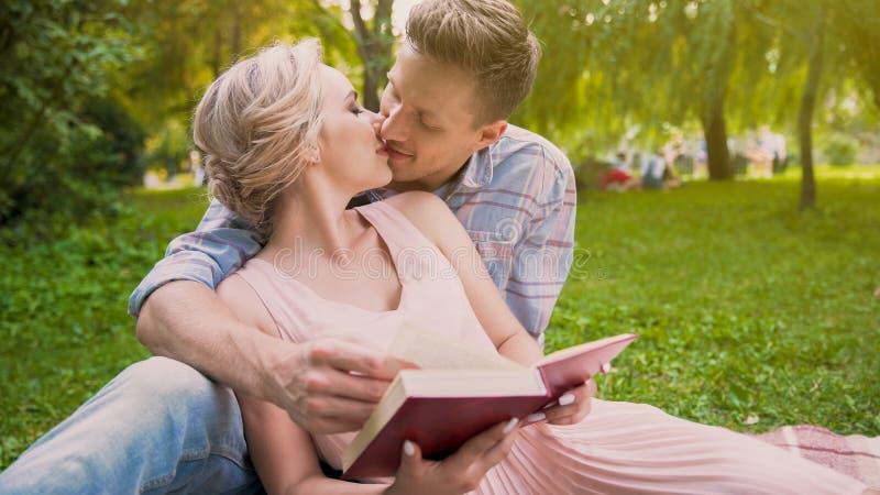 Pares en el amor que se sienta en el libro de lectura de la manta junto, suavemente besándose en roturas foto de archivo