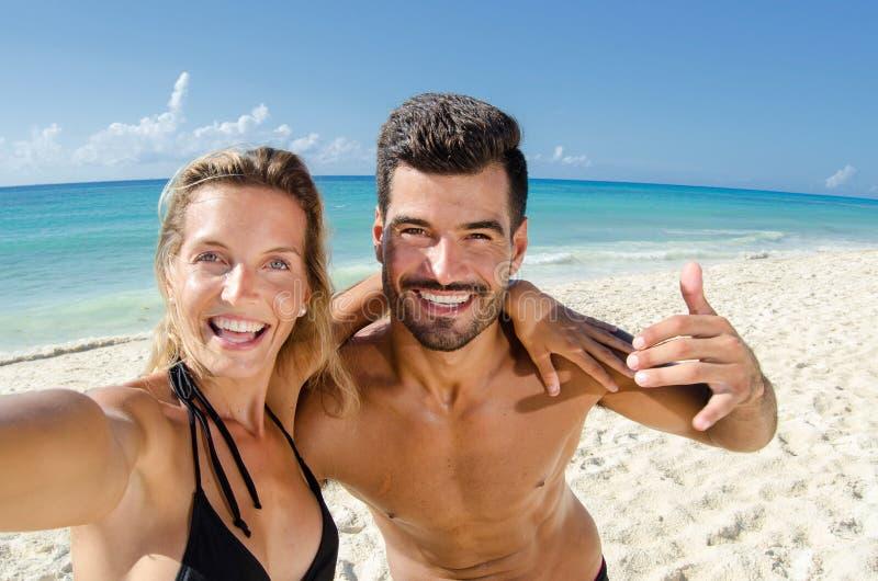 Pares en el amor que toma la foto del selfie en la playa fotos de archivo