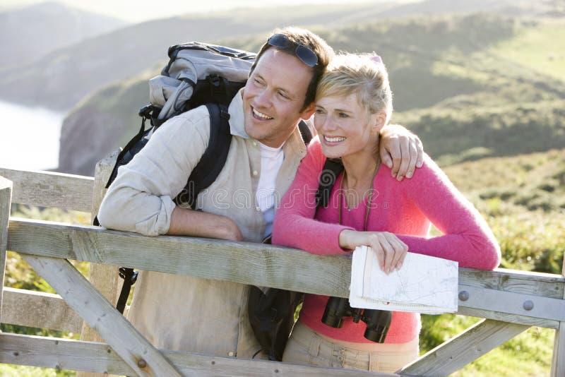 Pares en el cliffside al aire libre que se inclina en el pasamano fotografía de archivo