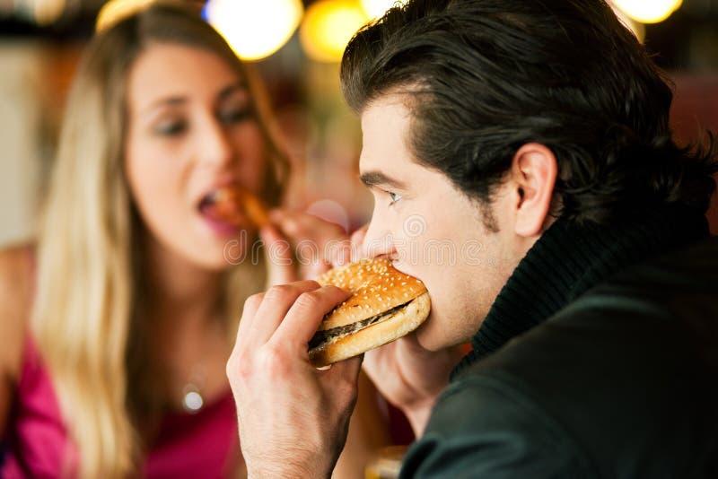 Pares en el restaurante que come los alimentos de preparación rápida