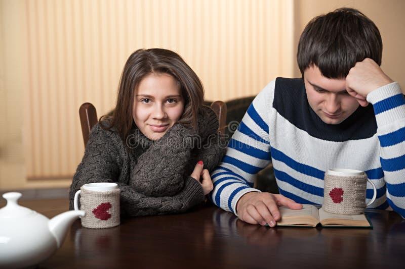 Pares en el té de consumición y la lectura de la tabla de un libro imagenes de archivo