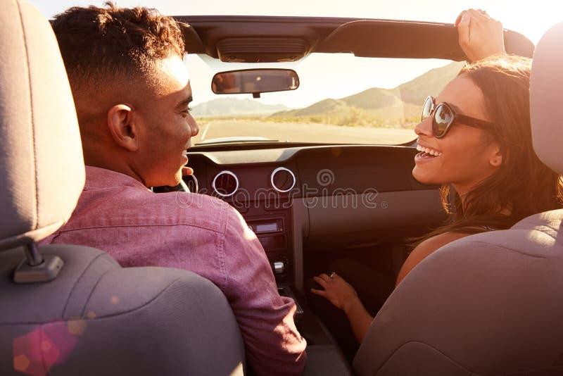 Pares en el viaje por carretera que conduce en coche convertible imagen de archivo
