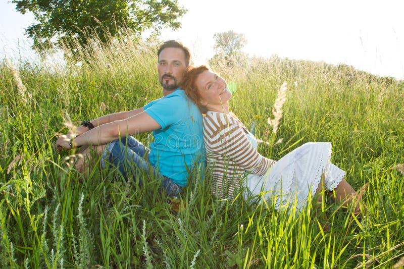 Pares en hierba verde grande de nuevo a la parte posterior Hombre y mujer que se sientan en el campo en día de verano fotografía de archivo libre de regalías