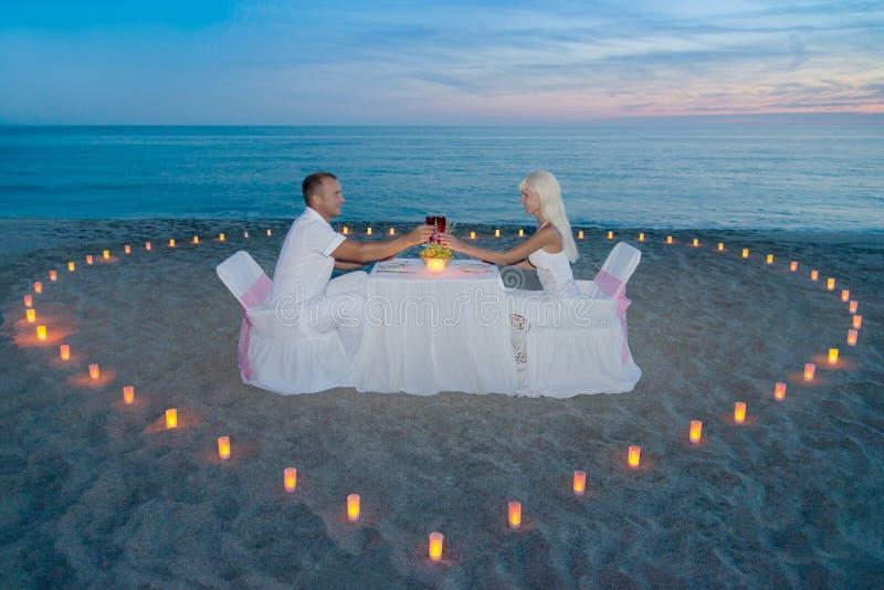 Pares en la cena romántica de la playa con el corazón de las velas imagenes de archivo
