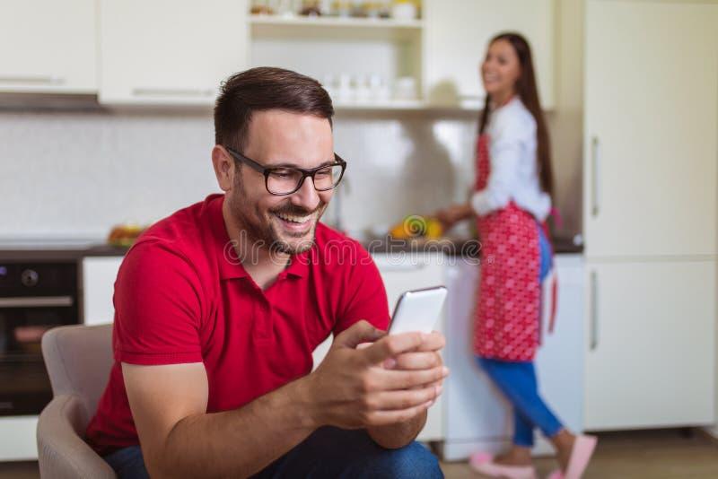 Pares en la cocina Hombre mientras que comprueba el teléfono móvil, mujer que prepara el desayuno fotos de archivo