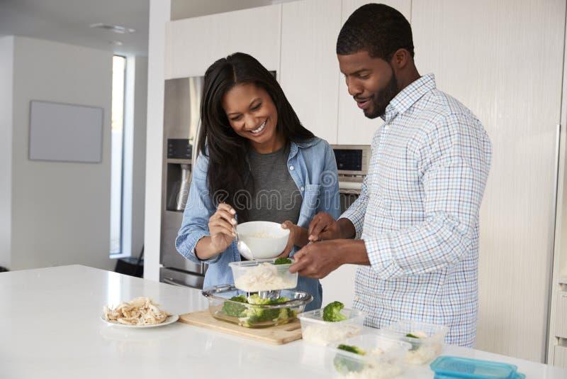 Pares en la cocina que prepara la comida de alto valor proteico y que pone porciones en los envases de plástico imagen de archivo