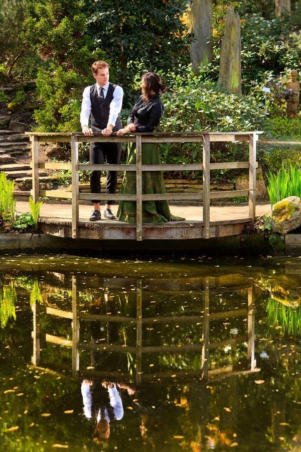 Pares en la moda victoriana cerca del lago con reflexiones en parque imágenes de archivo libres de regalías