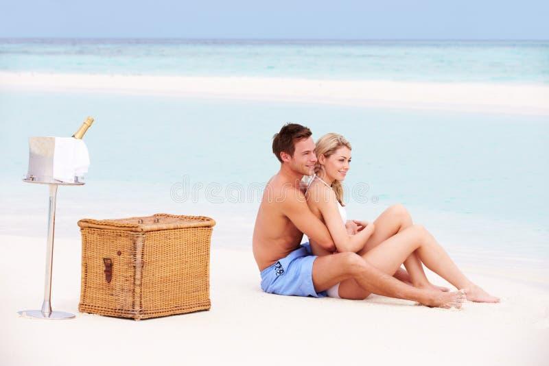 Pares en la playa con Champagne Picnic de lujo imagen de archivo