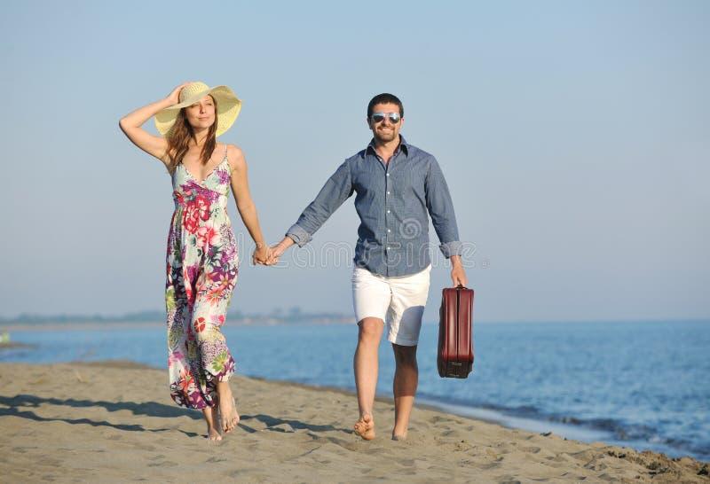 Pares en la playa con el bolso del recorrido foto de archivo
