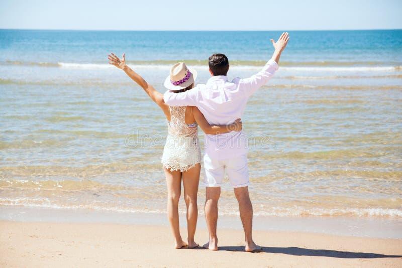 Pares en la playa para su luna de miel imagenes de archivo