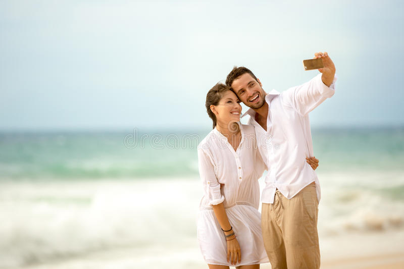 Pares en la playa que toma la foto de ellos mismos foto de archivo libre de regalías