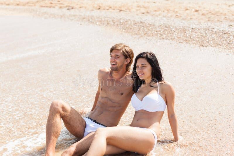 Pares en la playa, sentándose en abrazo del agua imágenes de archivo libres de regalías