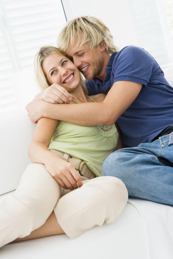 Pares en la sala de estar que abraza y que sonríe fotos de archivo libres de regalías