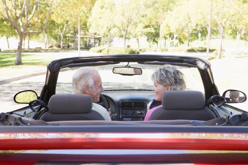 Pares en la sonrisa convertible del coche fotografía de archivo libre de regalías
