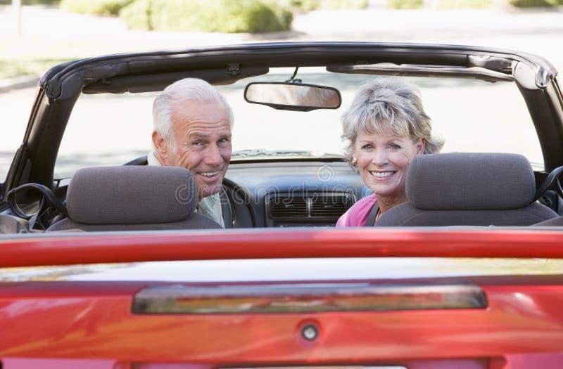 Pares en la sonrisa convertible del coche foto de archivo