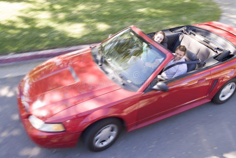 Pares en la sonrisa convertible del coche imagen de archivo libre de regalías
