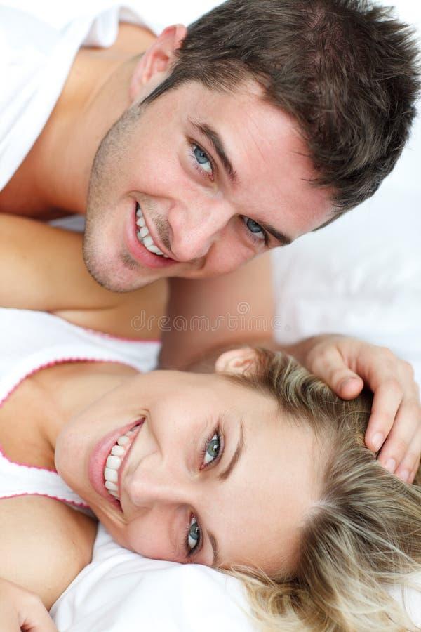Pares en la sonrisa de la cama fotos de archivo libres de regalías
