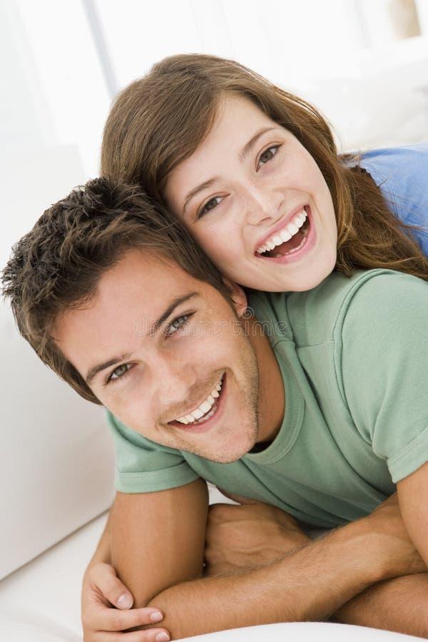 Pares en la sonrisa de la sala de estar foto de archivo