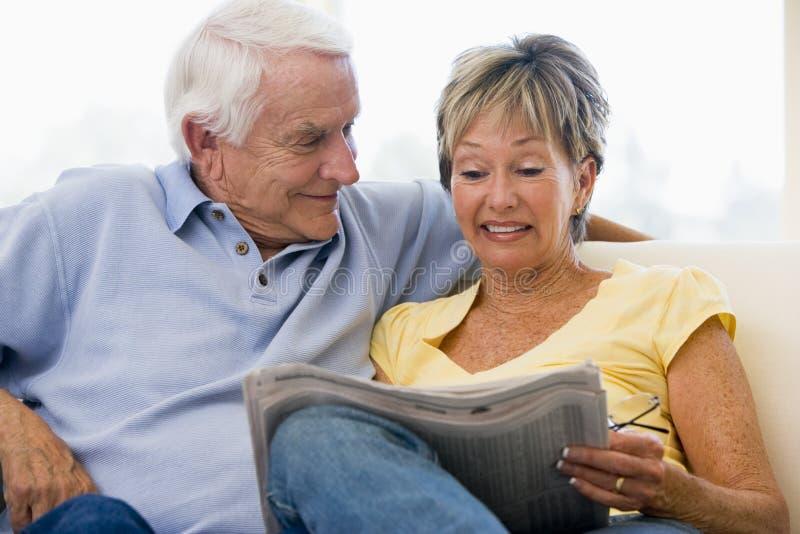 Pares en la sonrisa del periódico de la lectura de la sala de estar fotos de archivo libres de regalías