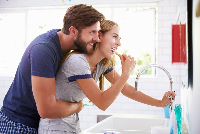 Pares en los pijamas que cepillan los dientes en cuarto de baño fotografía de archivo