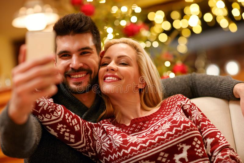 Pares en los suéteres calientes que toman la imagen del selfie con smartphone en fotografía de archivo