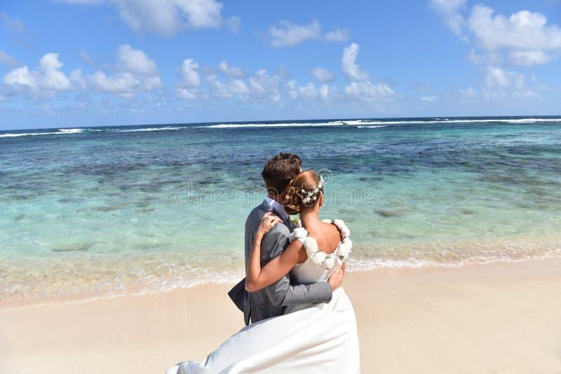 Pares en los vestidos de boda que miran el mar imágenes de archivo libres de regalías