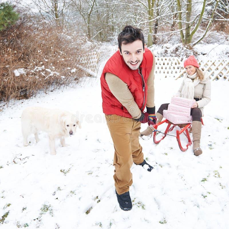 Pares en nieve con los regalos y el trineo de la Navidad fotografía de archivo