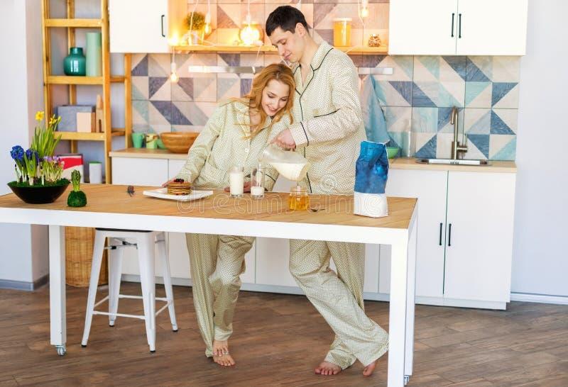 Pares en pijamas por la mañana en la cocina fotografía de archivo