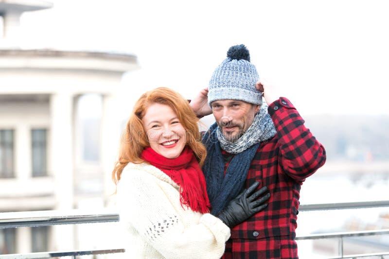 Pares en rojo Individuo en sombrero y muchacha roja del pelo La mujer feliz abraza al hombre El individuo vistió el sombrero y a  fotos de archivo