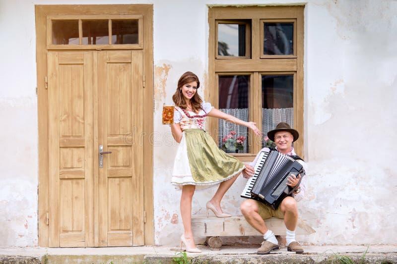 Pares en ropa bávara tradicional con la cerveza y el acordeón fotografía de archivo